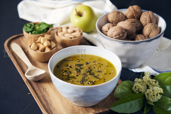 From above of tasty vegan cream soup with pumpkin seeds arranged on wooden tray with bread croutons and fresh basil placed on table near apples and walnuts