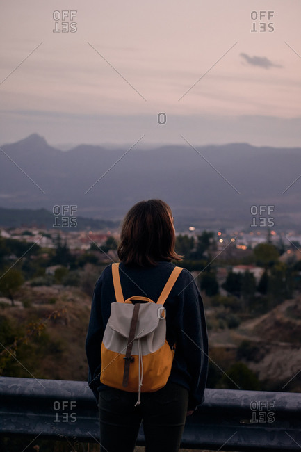 Back view of unrecognizable female traveler with backpack admiring view of village in mountain valley under sundown sky