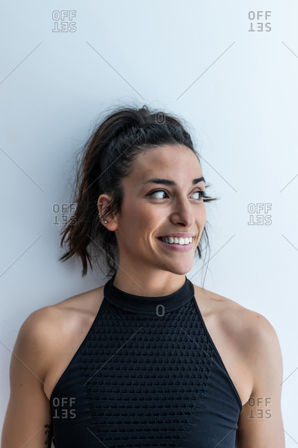 Cheerful ethnic female with ponytail and ear piercing tenderly smiling and looking away on white background