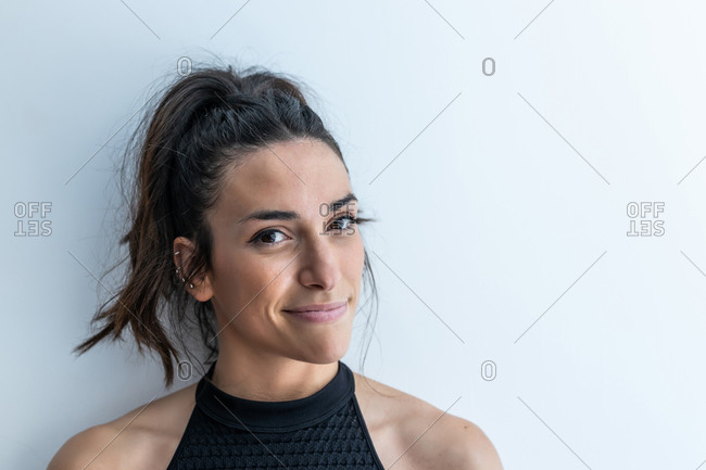 Cheerful ethnic female with ponytail and ear piercing tenderly smiling and looking at camera on white background