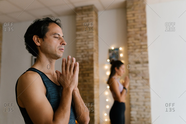 Side view of adult man meditating with closed eyes and clasped hands during group yoga lesson in studio