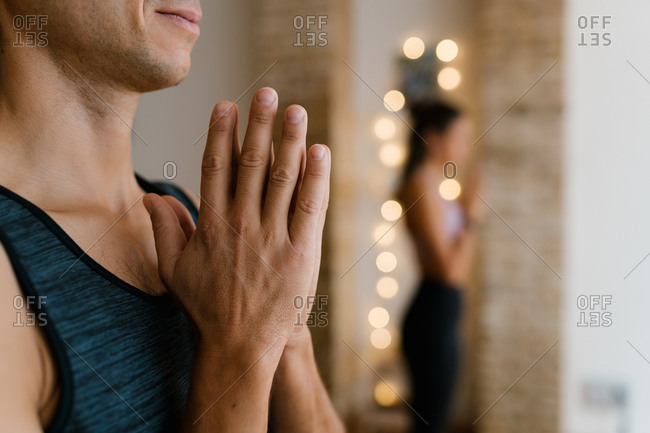 Side view of cropped unrecognizable adult man meditating with clasped hands during group yoga lesson in studio