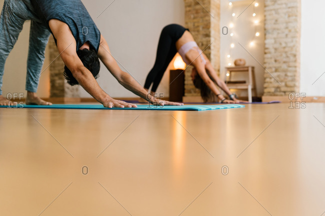 Unrecognizable people doing Downward Facing Dog pose with outstretched arms during group yoga lesson