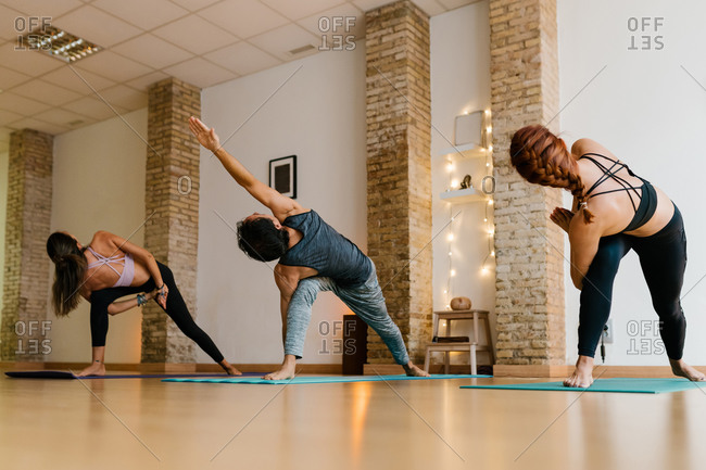 Slim barefoot women and man doing various yoga poses while practicing yoga in studio together