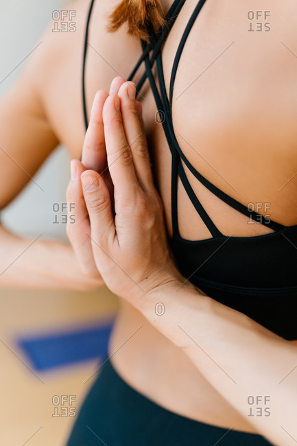 Soft focus of anonymous female clasping hands behind back while meditating during yoga lesson in studio