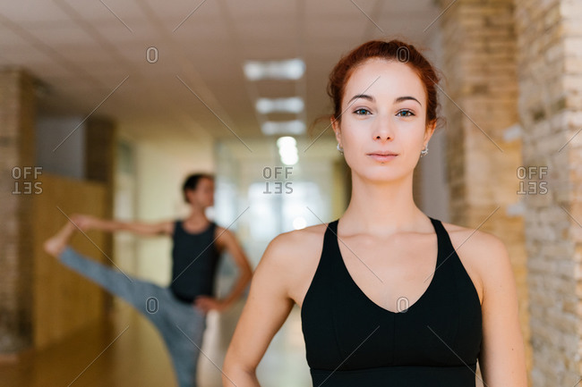 Young female looking at camera on blurred background of yoga studio during group lesson
