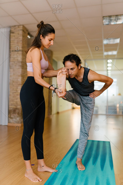 Full body female instructor supporting adult man doing Hasta Padangusthasana pose during yoga lesson in studio