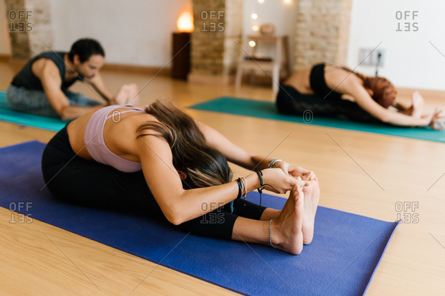 Anonymous barefoot female in sportswear sitting on mat and doing Pascimottanasana pose with group in yoga studio