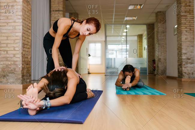 Female instructor pressing back of woman doing Seated Three Limbed Forward Bend during group yoga lesson in spacious studio