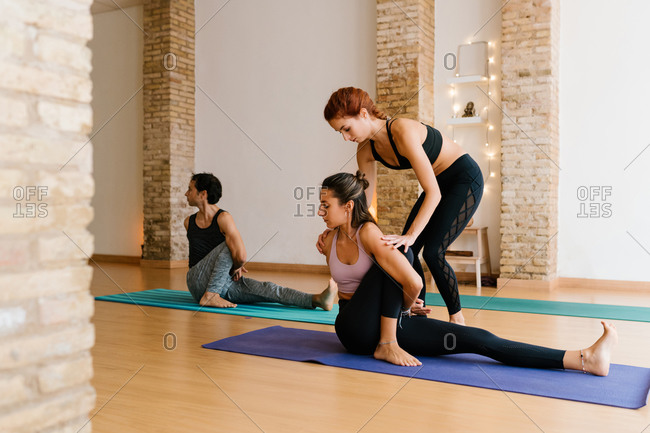 Fit female instructor supporting young woman doing Marichyasana pose while practicing yoga in studio