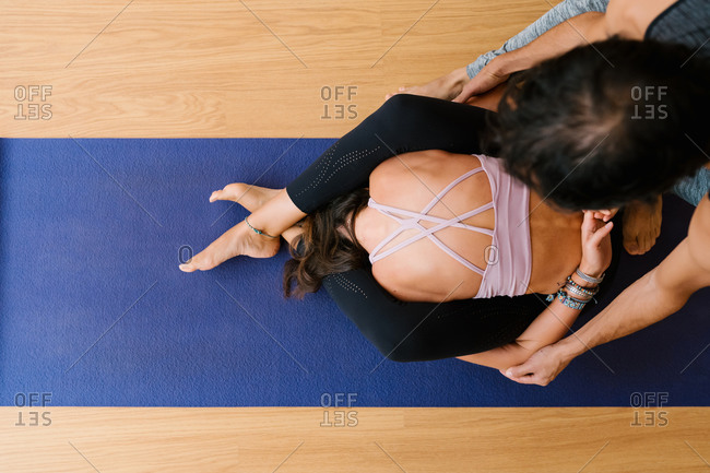 From above cropped unrecognizable male instructor helping woman to do Dvi Pada Sirsasana pose during yoga lesson in studio