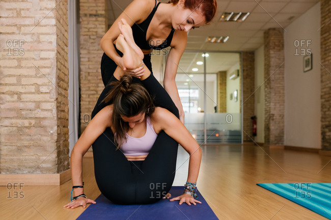 Crop female instructor helping woman to do Dvi Pada Sirsasana pose during yoga lesson in studio