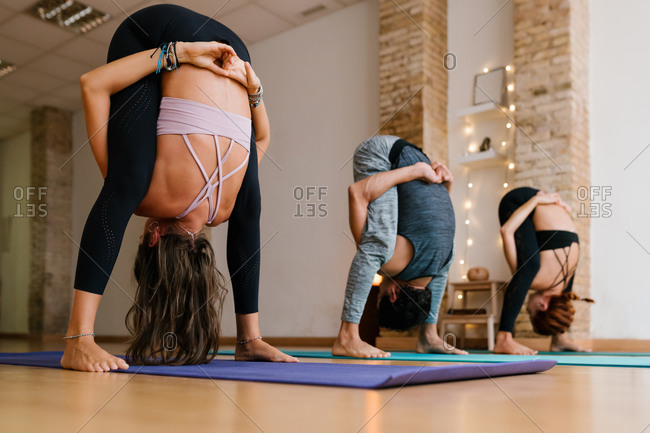 Ground level of group of anonymous slim people doing Uttanasana pose while practicing yoga in modern studio together