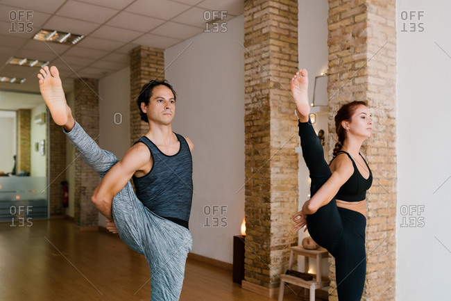 Adult male and young female in sportswear doing Svarga Dvirjasana pose during group yoga lesson in studio