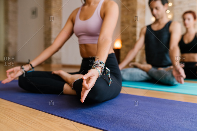 Anonymous female sitting on mat in Lotus pose and meditating with group during yoga lesson in studio