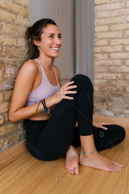 Barefoot young female in sportswear sitting on floor near brick wall and smiling during break in yoga studio