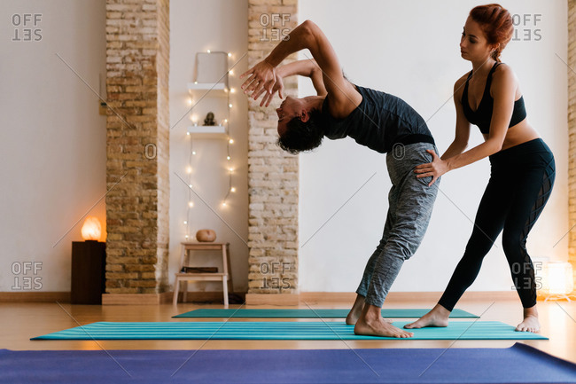 Young female instructor helping adult male to do Wheel pose during yoga lesson in studio