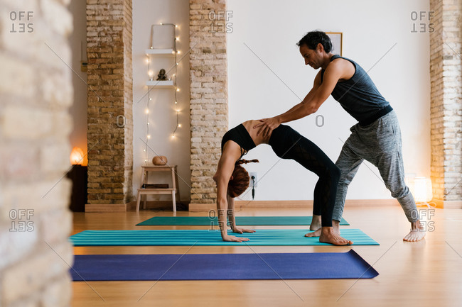 Young male instructor helping adult female to do Wheel pose during yoga lesson in studio