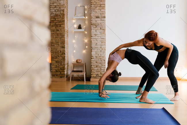 Young female instructor helping adult woman to do Wheel pose during yoga lesson in studio
