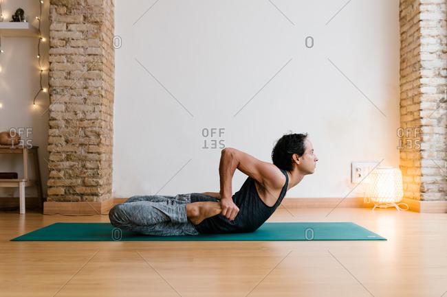Side view of ethnic guy in sportswear preparing to do Dhanurasana pose on mat in yoga studio