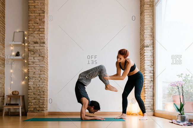 Young female trainer supporting man doing Vrschikasana pose during yoga lesson in cozy studio