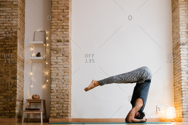Side view of unrecognizable barefoot male doing Salamba Sirsasana pose during yoga lesson in cozy studio