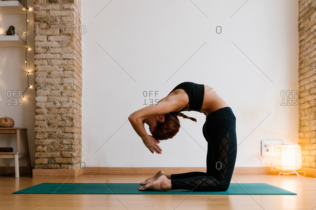 Side view of slim young female in sportswear clasping hands and bending back while doing Ustrasana pose in studio