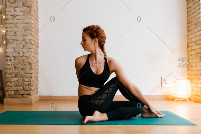 Young female in sportswear twisting body and doing Ardha Matsyendrasana pose on mat while practicing yoga in studio