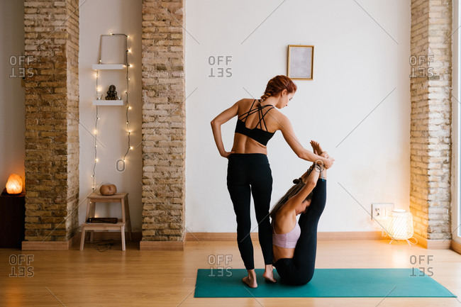 Slim female coach supporting woman doing Boat with Thighs to Chest pose during yoga lesson in cozy studio