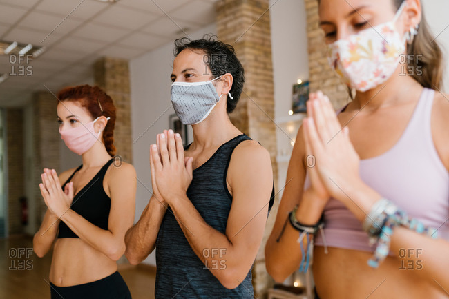 Group of people in face masks gesturing namaste and looking away at start of yoga lesson in studio during pandemic
