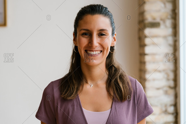Adult happy woman looking at camera during break in yoga lesson in studio