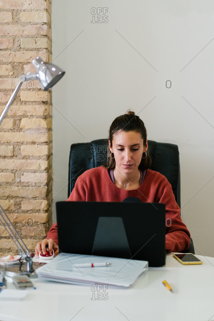 Focused young female in casual clothes smiling and browsing data on computer in cozy workspace