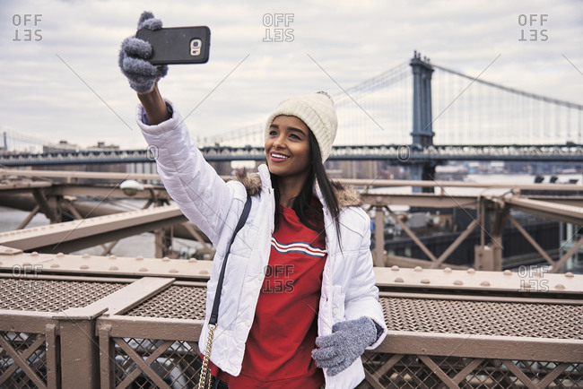 Cheerful African American woman in warm clothes taking photo on selfie camera of smartphone while standing on street of New York