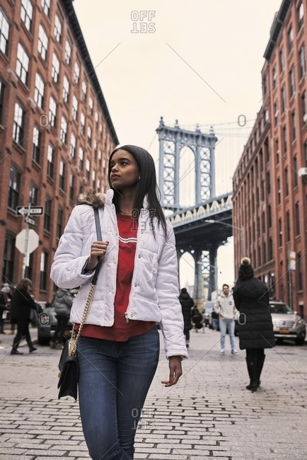 Calm African American female in white warm jacket standing on street of New York and looking away