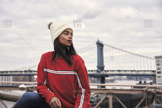 Tranquil African American female in warm outerwear leaning on metal bridge and looking away during stroll in New York city