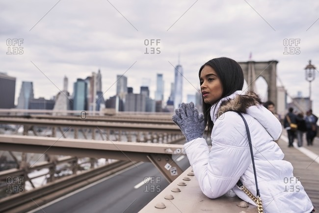 Side view of tranquil African American female in warm outerwear leaning on metal bridge and looking away during stroll in New York city