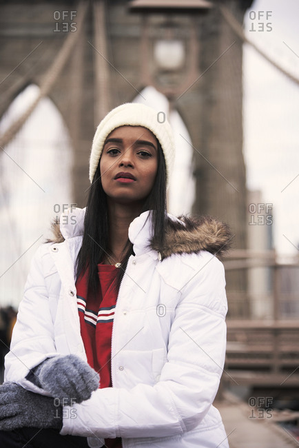 Thoughtful African American female wearing white warm jacket sitting on Brooklyn bridge and looking at camera while enjoying cityscape