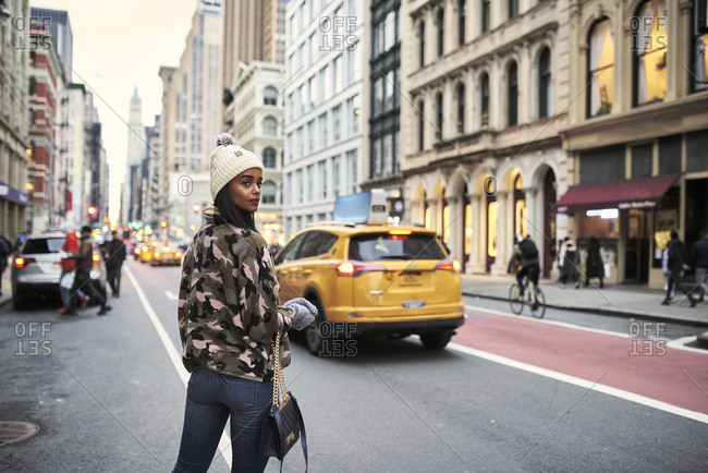 Back view of African American female in stylish warm clothes crossing road in New York during stroll and looking over shoulder