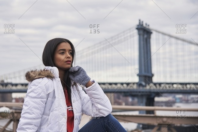 Tranquil African American female in warm outerwear near metal bridge and looking away during stroll in New York city