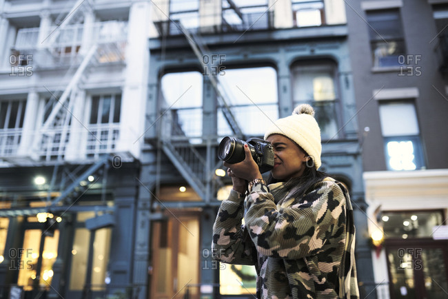 Low angle of African American female photographer in warm hat and stylish sweater taking picture of modern photo camera in New York city