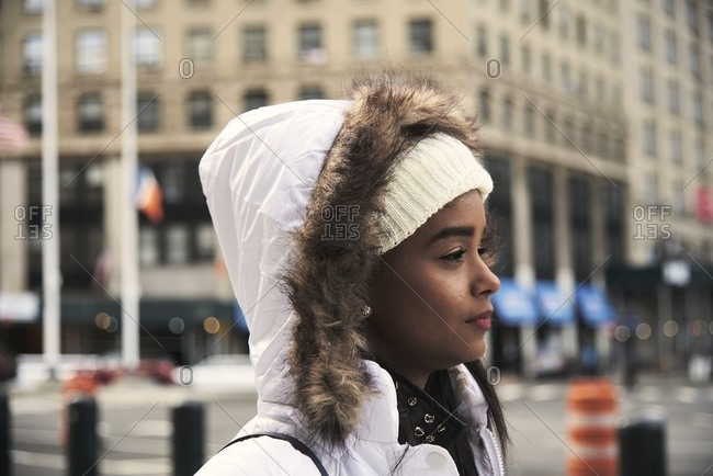 Side view of young African American female in outerwear walking along street in New York and enjoying stroll