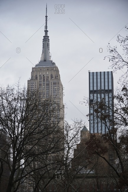 December 14, 2018: From below of tall skyscraper with illuminated windows on background of gray sky in New York