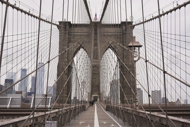 Symmetric view of suspension Brooklyn bridge with cables and gates on cloudy day in New York