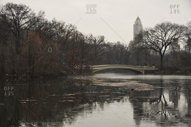 Bow Bridge over calm lake in Central Park on cloudy day in fall in New York