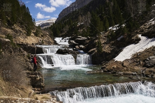 Side view of anonymous traveler admiring view of amazing cascade waterfall in Pyrenees mountain range in Ordesa Valley