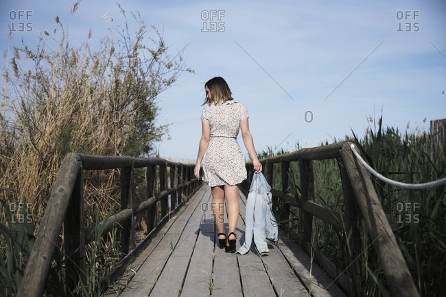 Full body back view of young female in casual dress with jacket in hand strolling on wooden footbridge among tall dry grass in sunny day