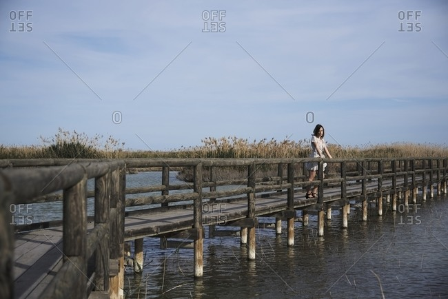 Unrecognizable distant female in dress resting alone on wooden boardwalk near lake and enjoying summer day in nature