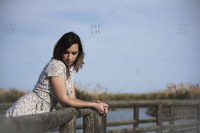 Young brunette female in dress resting alone on wooden boardwalk near lake and enjoying summer day in nature