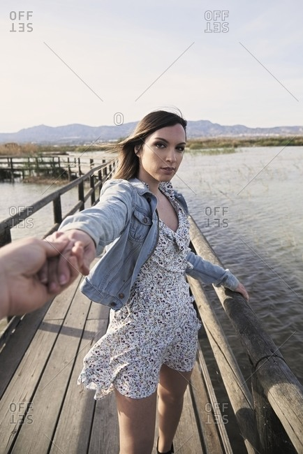 Young female traveler in casual dress and denim jacket holding hand of anonymous friend and inviting to follow her while standing on wooden walkway over lake