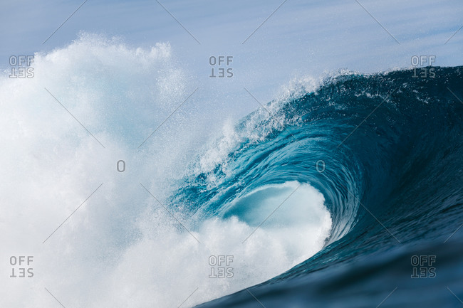 Powerful foamy sea waves rolling and splashing over water surface against cloudy blue sky